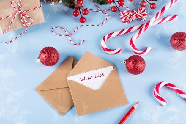 Tekst verlanglijst. envelop, papieren kaart en decoratie op blauwe tafelbladweergave.