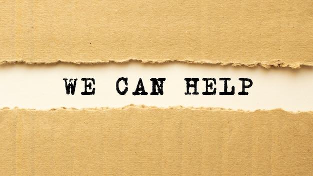 Tekst we can help verschijnt achter gescheurd bruin papier