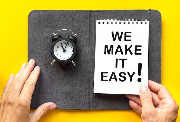 Tekst we make it easy vrouwenhand houdt het notitieboekje vast, kleine wekker. gele achtergrond met kopie ruimte.