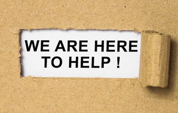 Tekst we zijn hier om te helpen achter gescheurd bruin papier.
