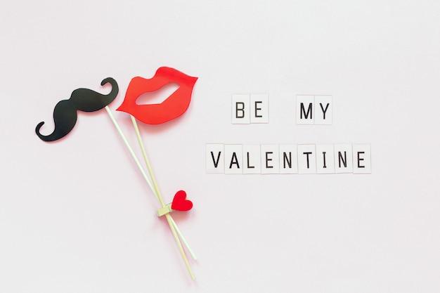 Tekst wees mijn valentijn en koppel papieren snor, lippensteunen bevestigd wasknijperhart op stok op roze