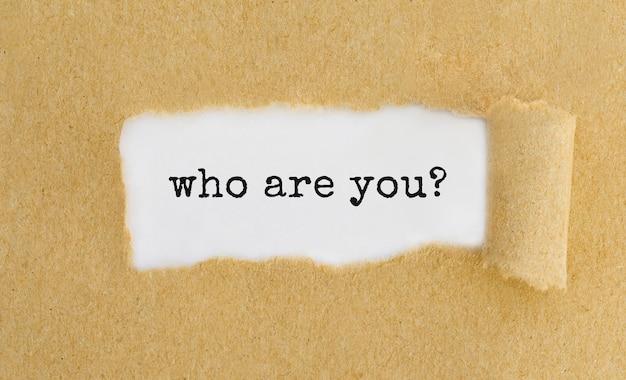 Tekst wie ben jij verschijnt achter gescheurd bruin papier