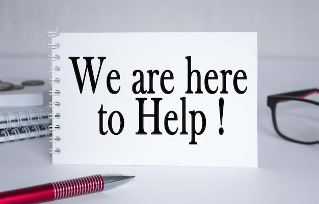 Tekst wij zijn hier om te helpen. kladblok met bril en tekstdocumenten. bedrijfsconcept