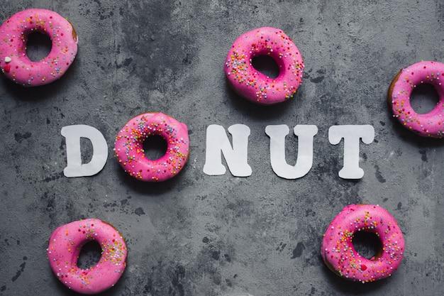 Tekst woord donut gemaakt van een roze regenboog hagelslag donut en witboek letters op grijs donker