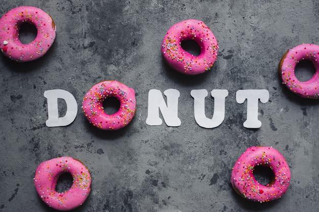 Tekst woord donut gemaakt van een roze regenboog hagelslag donut en witboek letters
