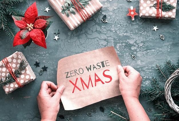 Tekst zero waste xmas op ambachtelijk papier. plat lag, top uitzicht op grijze achtergrond. diy kerstcadeaus en handgemaakte decoraties.