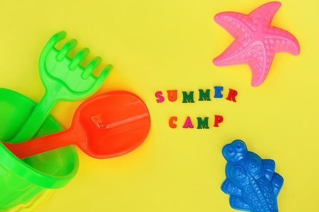 Tekst zomerkamp en veelkleurig set kinderspeelgoed voor de zomer spelen ent