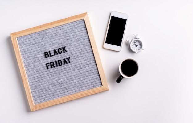 Tekst zwarte vrijdag op grijs brievenbord met mobiele telefoon, koffie en wekker