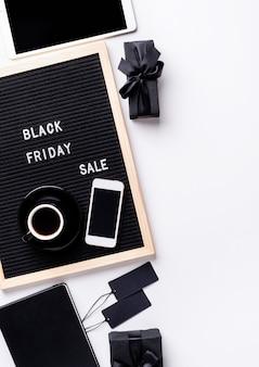 Tekst zwarte vrijdag verkoop op zwart letterbord met kopje koffie, smartphone, prijskaartjes