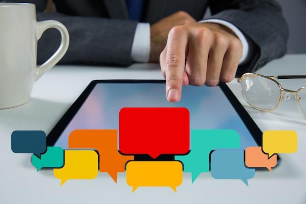 Tekstballonnen met zakenman werkt op zijn tablet