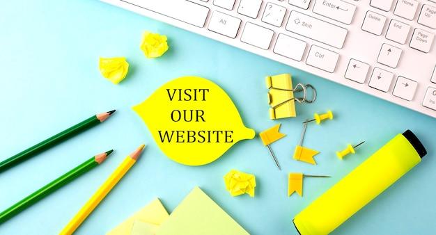 Tekstbord met bezoek onze website met kantoorhulpmiddelen en toetsenbord op de blauwe achtergrond