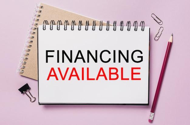 Tekstfinanciering beschikbaar op een witte blocnote met de achtergrond van kantoorbenodigdheden. plat op concept voor zaken, financiën en ontwikkeling