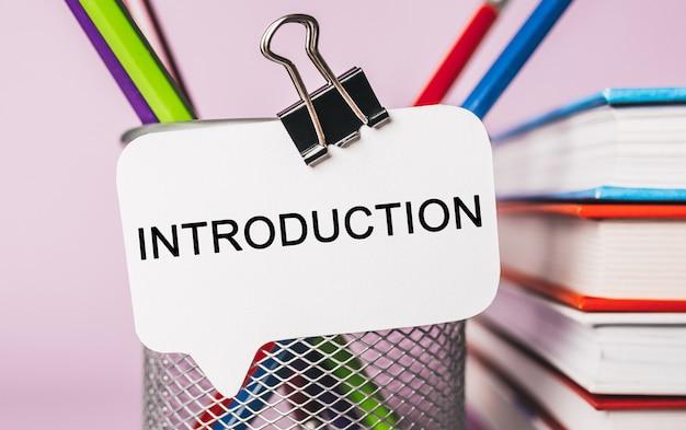 Tekstintroductie op een witte sticker met de achtergrond van kantoorbenodigdheden. plat leggen op concept voor zaken, financiën en ontwikkeling