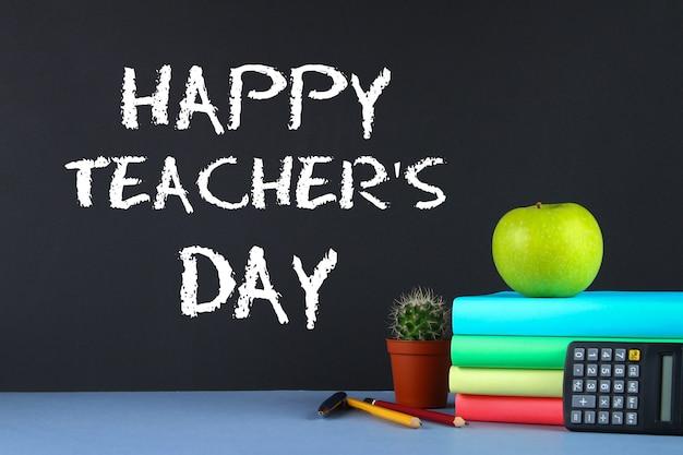 Tekstkrijt op een schoolbord: happy teacher's day. schoolbenodigdheden, kantoor, boeken, appel.