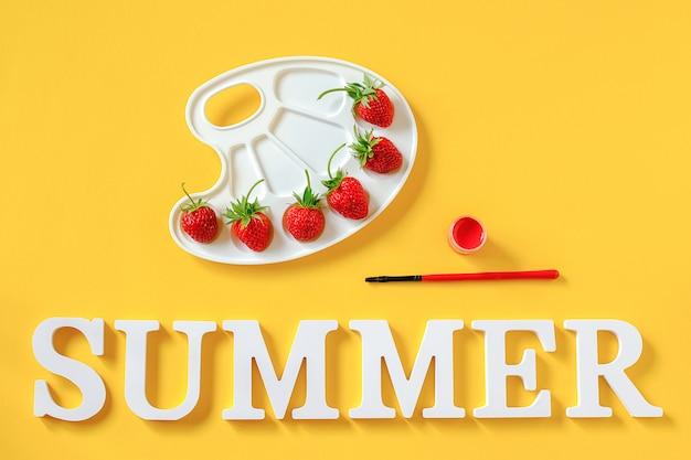 Tekstzomer, rode rijpe aardbeien op een artistiek palet, penseel en gouache op gele achtergrond
