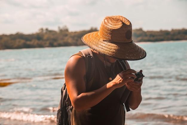 Tela, honduras: een jonge man met een hoed op het strand van punta de sal in de caribische zee met een actiecamera