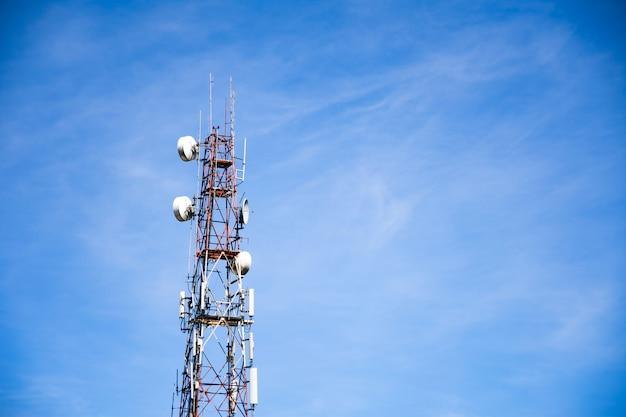 Telecommunicatie toren draadloze technologie tegen blauwe lucht en wolken.
