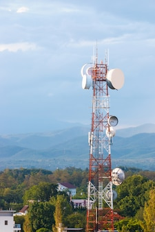 Telecommunicatietoren tegen bewolkte blauwe hemel en verre bergen