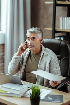 Telefonisch gesprek. aangename knappe man die aan de telefoon praat terwijl hij zijn werk bespreekt