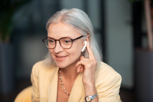 Telefonisch gesprek. close-upportret van een glimlachende hogere zakendame die een lichtgeel jasje en een gouden ketting draagt die aan de telefoon spreekt