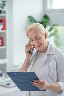 Telefonisch raadplegen. blonde arts die een verre consultaion op de telefoon heeft