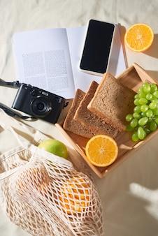 Telefoon, camera, fruit, tas, notebook en accessoires, bovenaanzicht, plat leggen, het concept van een picknick, zomer