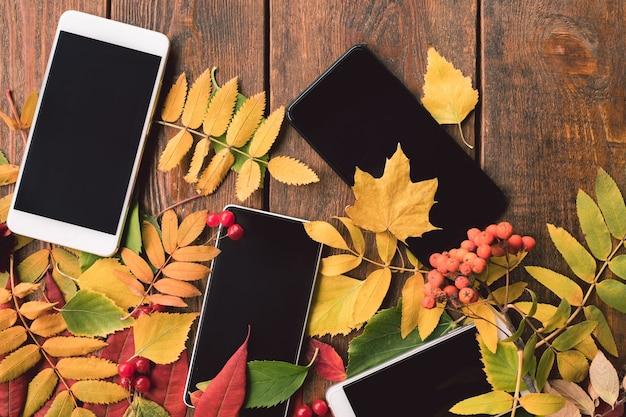 Telefoon e-commerce advertentie concept. herfstbladeren op houten muur