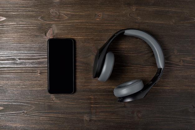 Telefoon en koptelefoon op een donkere houten achtergrond. het opdrogen van de muziek. bovenaanzicht