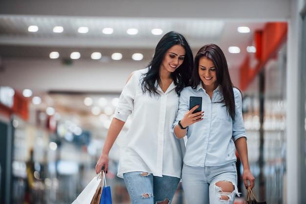 Telefoon gebruiken. twee jonge vrouwen hebben samen een dagje winkelen in de supermarkt.