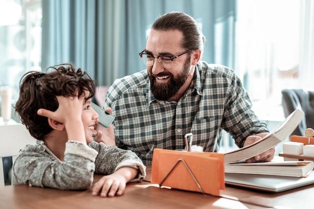 Telefoon geven. bebaarde donkerharige vader die zijn zoon blauwe smartphone geeft om met moeder te praten