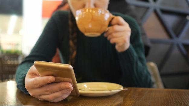 Telefoon in de hand van het meisje in focus, vrouw drinkt koffie op de onscherpe achtergrond.