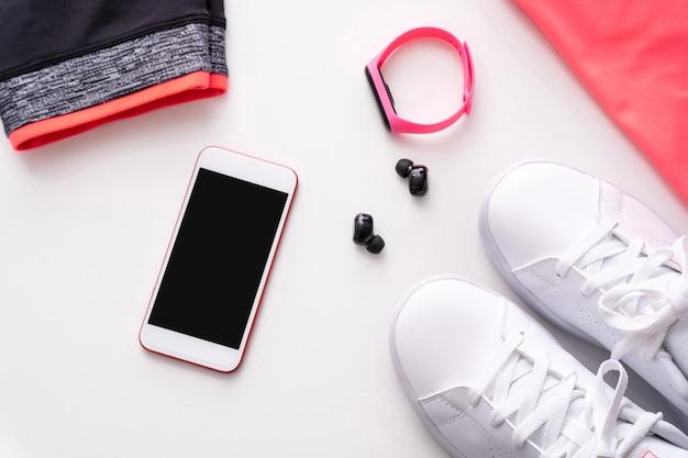 Telefoon, koptelefoon, horloge met sportkleding en sneakers op witte achtergrond