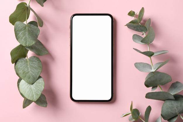 Telefoon met leeg scherm en plant op roze oppervlak