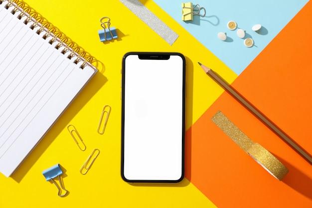 Telefoon met leeg scherm op kleur versierde achtergrond, bovenaanzicht