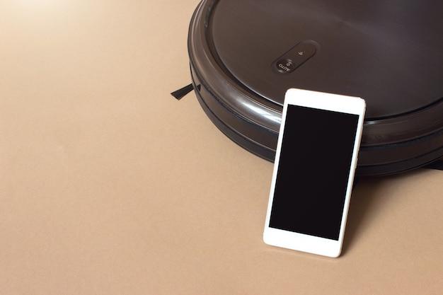 Telefoon met mobiele app om robotstofzuiger te bedienen. schoonmaakrobot voor thuis. slim leven