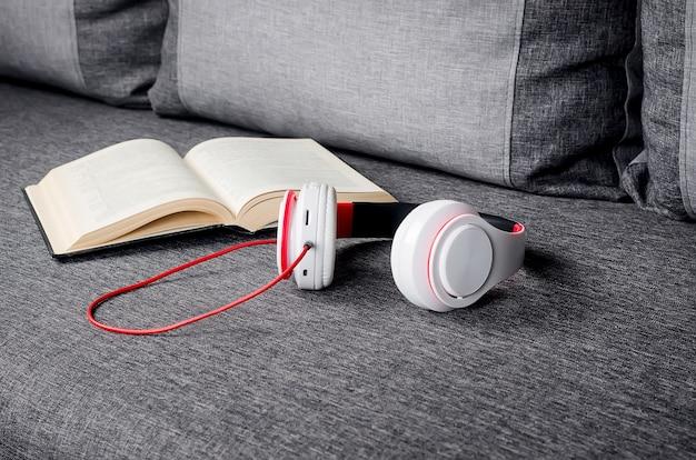 Telefoon met oortelefoons en boek als audioboekconcept