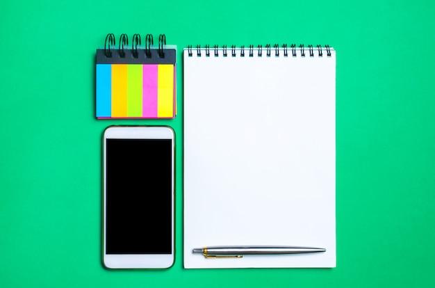 Telefoon, notitieboekje, pen en stickers op de schoolbank