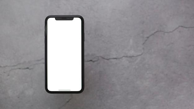 Telefoon op grijze achtergrond met wit scherm voor kopie-ruimte.