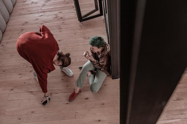 Telefoon van vriendin. jaloerse boze en gekke vriend die telefoon neemt van vriendin die op de vloer zit