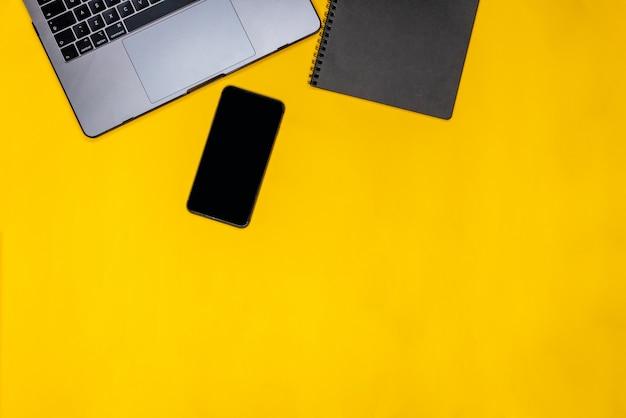 Telefoon, zwarte blocnote en laptop
