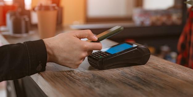 Telefoonbetalingsclose-up van een klant die een smartphone aan een betaalterminal bevestigt om voor koffie in een café te betalen