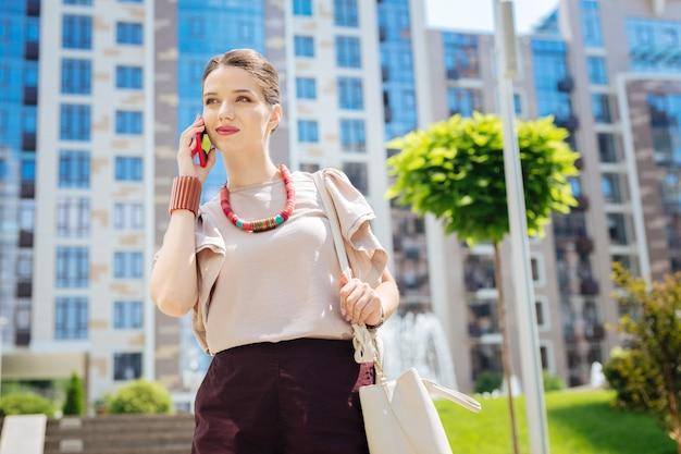 Telefoongesprek. aangename aardige vrouw die lacht tijdens een telefoongesprek