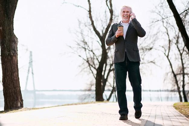 Telefoongesprek. lage hoek van ervaren senior zaken man in park gaan en praten over de telefoon