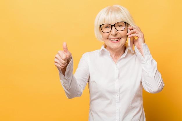 Telefoongesprek. positieve oude vrouw die lacht tijdens het praten aan de telefoon geïsoleerd op gele achtergrond. duimen omhoog.