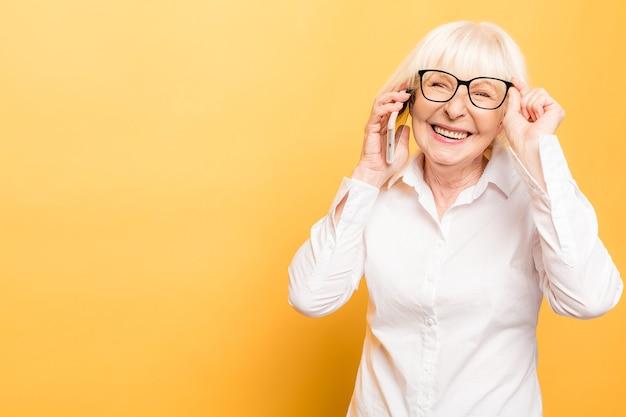 Telefoongesprek. positieve oude vrouw die lacht tijdens het praten aan de telefoon geïsoleerd op gele achtergrond.