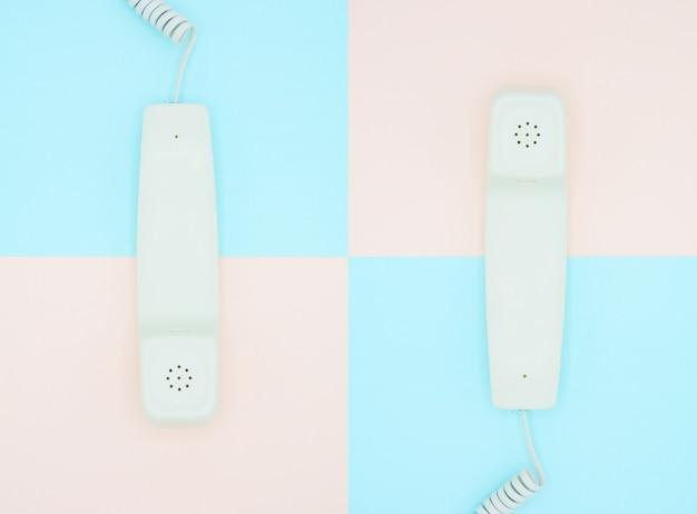 Telefoonhoorn op blauwe en roze achtergrond