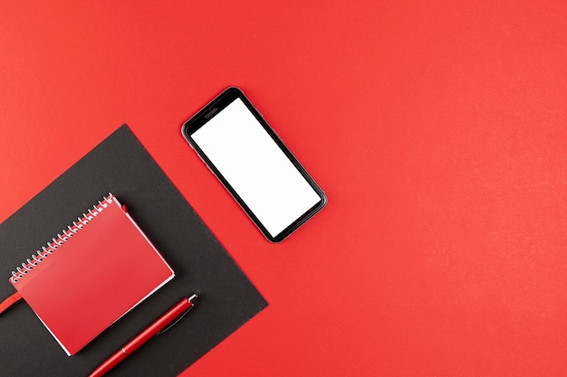 Telefoonmodel naast rood notitieboekje