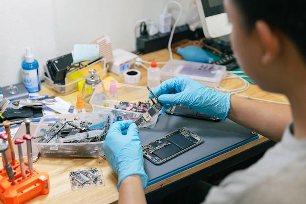 Telefoonreparatieconcept een reparateur die het elektronische onderdeel plukt om te monteren met de mobiele telefoon met de tools op het bureau.