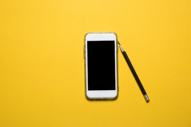 Telefoons, communicatie-apparaten geplaatst op een gele achtergrond technologie concept met kopie ruimte