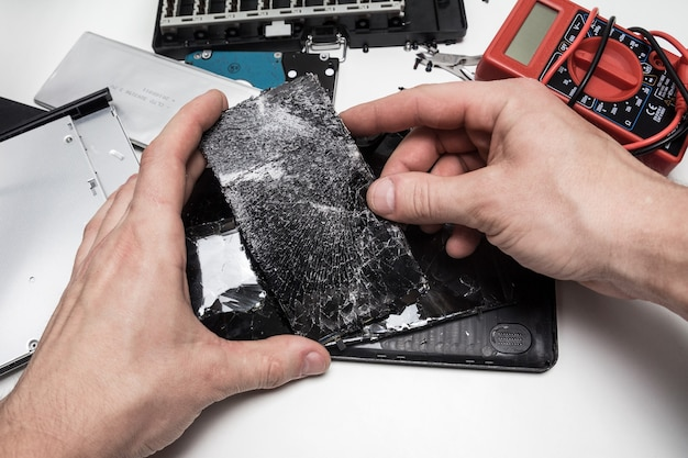 Telefoons repareren in een werkplaats, kapot telefoonscherm, voorbereidingen treffen om het display op de telefoon te vervangen